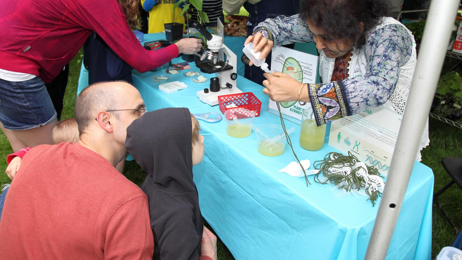 ABRC's Gauri Datta helps a young visitor extract DNA from applesauce