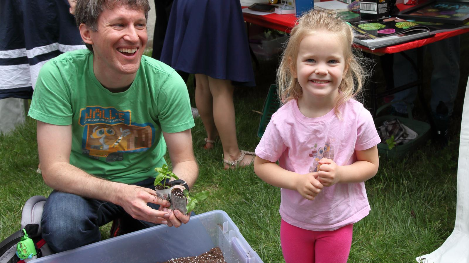 A father and daughter plant basil at WestFest 2018